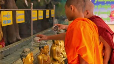 MANDALAY, MYANMAR - 13 JAN 2014: Monks watered Buddha statues. Each statue corresponds to the day of the week — Vídeo Stock
