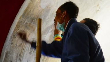 BAGAN, MYANMAR - CIRCA JAN 2014: Professional restorers working with paintings of the ancient temple — Stock Video