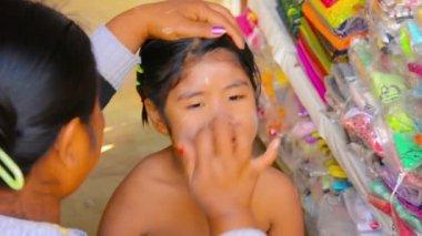 BAGAN, MYANMAR - CIRCA JAN 2014: Mother applies sunscreen thanaka on her daughter's face — Stock Video