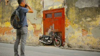 GEORGE TOWN, PENANG, MALAYSIA - 22 JUL 2014: Boy on a Bike - wall painting and a tourist with a camera — Stock Video