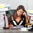 Over-worked woman in office — Stock Photo