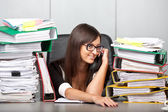 Over-worked woman in office, speaking on phone. — Stock Photo