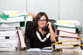 Over-worked woman in office. speaking on phone. — Stock Photo