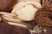 Fresh bread and wheat on the wooden — Stock Photo