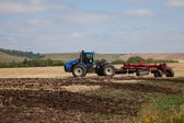 The tractor plowing a field — Stock Photo