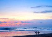 Couple of surfers walking on the beach — Stok fotoğraf
