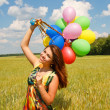 Happy young woman and colorful balloons — Stock Photo #18044103