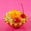 Sweet cake with fruits on pink background — Stock Photo #18042993