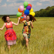 Happy young women and colorful balloons — Stockfoto