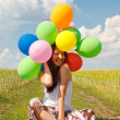Happy young woman and colorful balloons — Stockfoto