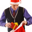 Young businessman in santa hat offering a gift to you — Stockfoto