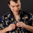 Young man fastens his shirt — Stock Photo
