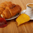 Autumn scene. Coffee and croissant on table — Stock Photo #18044085
