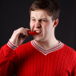 Young guy eats pepper — Stock Photo