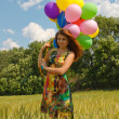 Happy young woman and colorful balloons — ストック写真