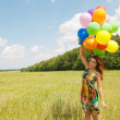 Happy young woman and colorful balloons — 图库照片