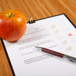 Test and an apple on a wooden table — Stock Photo