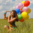 Happy young woman and colorful balloons — Stock fotografie