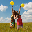 Happy young women and colorful balloons — Stock Photo