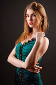 Studio portrait of a beautiful young woman in green dress — Stock Photo