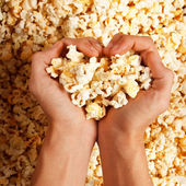 Hand looks out of popcorn — Stock Photo