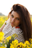 The young girl smells yellow flowers in the field — Stock Photo
