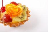 Söt tårta med frukter på vit bakgrund — Stockfoto