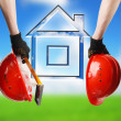 Construction hard hat in hand. House icon — Stockfoto