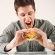 člověk jíst hamburger — Stock fotografie