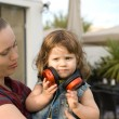 The little girl listen music with her mother — Stock Photo #29047117