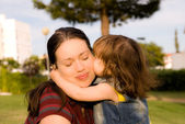 The little girl is kissing her mother — Stock Photo