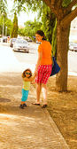 Mother with baby girl walking in street — Stock Photo