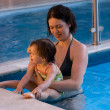 The baby girl play with her mother in pool — Stock Photo