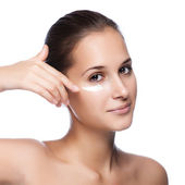 Portrait of beautiful woman applying cream on face - isolated on — Stock Photo
