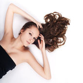 Beautiful girl with long hair lying on the floor — Stock Photo