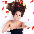 Beautiful woman with curly hair in the petals of roses — ストック写真