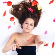 Stockfoto: Beautiful womwith curly hair in petals of roses