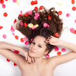 Stock Photo: Beautiful womwith curly hair in petals of roses
