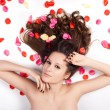 Beautiful woman with curly hair in the petals of roses — Foto de Stock