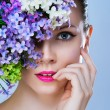 Black and white painted close-up portrait of girl with stylish makeup and flowers around her face — Stock Photo