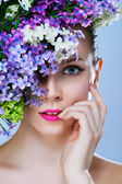 Black and white painted close-up portrait of girl with stylish makeup and flowers around her face — Stok fotoğraf