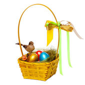 Colorful eggs in a wicker, over white background. — Stok fotoğraf