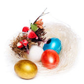 Colorful eggs in a wicker, over white background. — Stock fotografie
