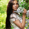 Young woman smelling lilac in spring park — Stock Photo #26034379
