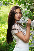 Young woman smelling lilac in spring park — Stockfoto