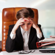 Tensed young business woman holding her head while at work — Stock fotografie