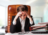 Tensed young business woman holding her head while at work — Stock Photo