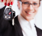 Business woman holding keys over white background — Stock Photo