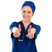 Sjuksköterskan visar tummen upp framgång tecken bär stetoskop och scrubs — Stockfoto