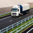 White truck on asphalt road under blue sky with clouds — Stockfoto